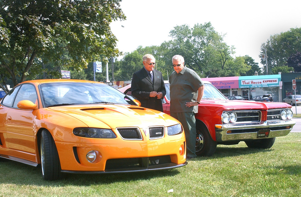 Description of . Kip Wasenko, Exec. Director of Advance Concept Studios for General Motors with a 2004 Pontiac GTO and Ken Orlowski of Romeo with his '64 GTO. The cas were on display at the kickoff of the 10th anniversary of the Woodward Dream Cruise.