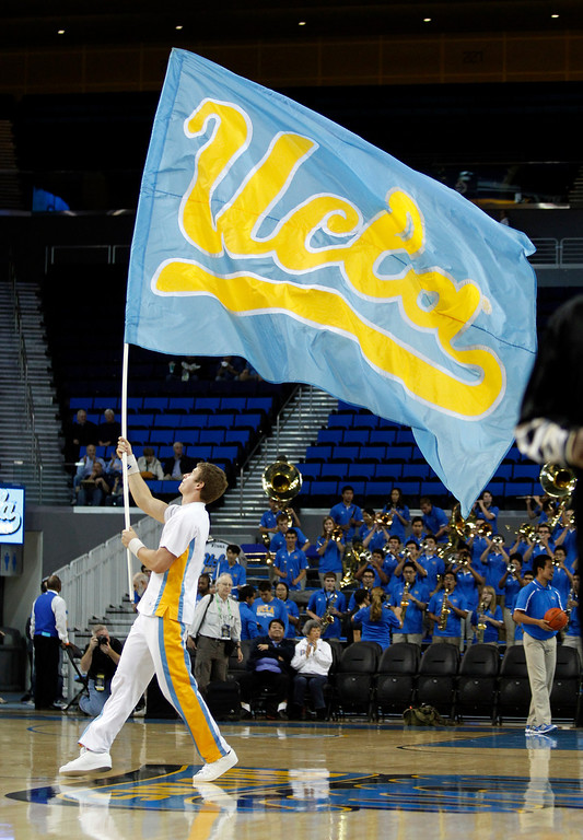 Description of . UCLA cheerleader displays a team banner prior to their NCAA college basketball game against Oakland Tuesday, Nov. 12, 2013, in Los Angeles. UCLA won the game 91-60.  (AP Photo/Alex Gallardo)