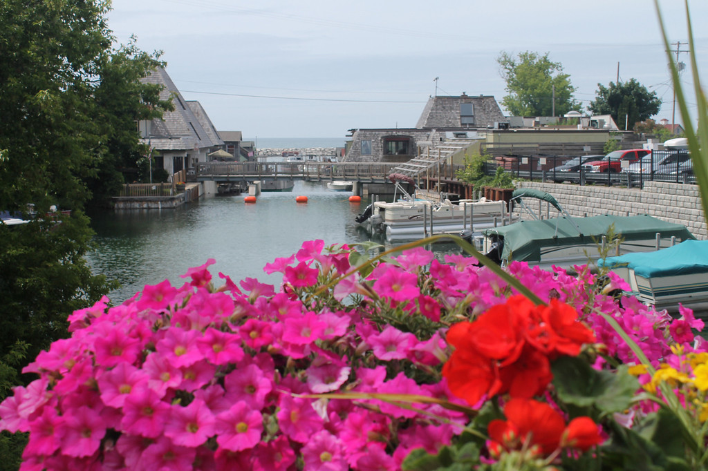 Description of . Leland, set on the Lake Michigan shore in Leelanau County, is a not-to-be-missed travel destination. Shown is a bridge over the Leland River looking out to Lake Michigan.  Photos by Kristine Morris
