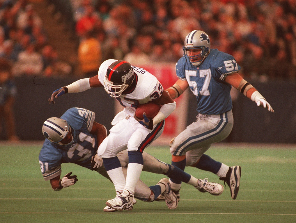 . Detroit Lions Cory Schlessinger(31) and Stephen Boyd  (57) gang tackle Erric Pegram (33) of the  New York giants late in the second half.