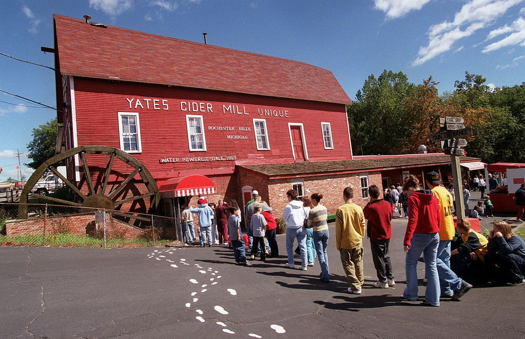 Description of . People wait in line to go inside the Yates Cider Mill barn to purchase cider, donuts, and other treats, Saturday, September 16, 2000.