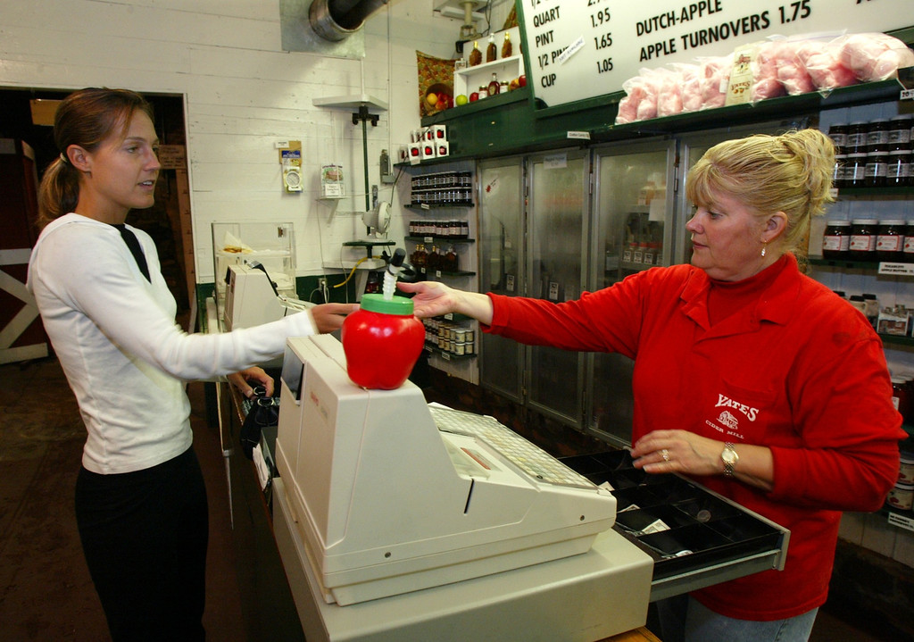 Description of . Shelley McLaren of Rochester Hills receives change from Doris Delmotte of Shelby Township during a visit to Yates Cider Mill. Photographed Monday, September 22, 2003.