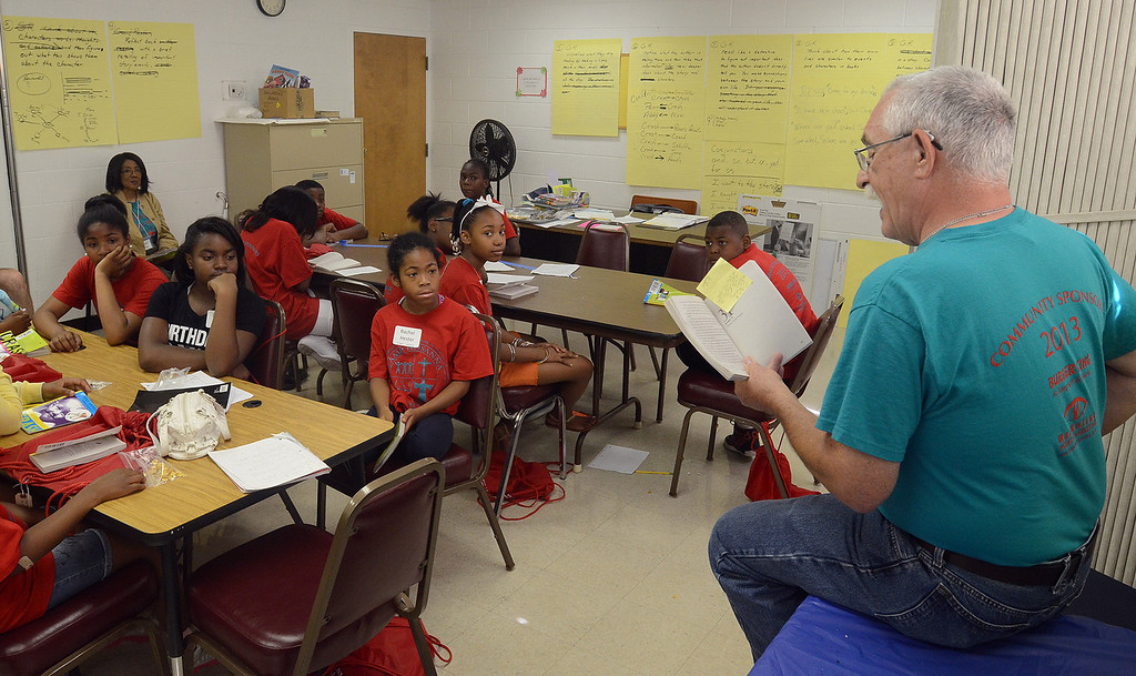 Description of . Stu Raben, of Commerce Twp., reads to kids during the free Camp Hosanna at New Bethel Missionary Baptist Church in Pontiac, Monday July 22, 2013. (Oakland Press Photo:Vaughn Gurganian)