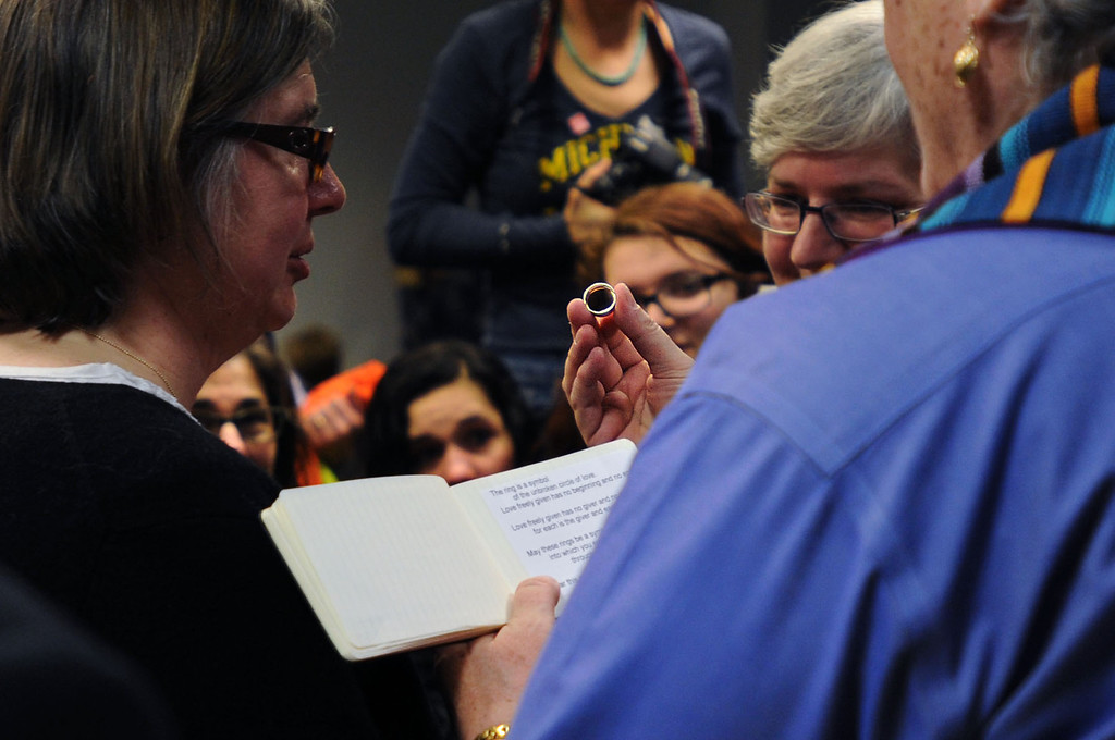 Description of . Gail Gaisenhaner holds up a wedding ring as she officiates a marriage between Beth Sherman and Karen Hawver of Ann Arbor at the Washtenaw County Clerk's office in Ann Arbor, Mich., Saturday, March 22, 2014, the day after a federal court struck down Michigan's ban on gay marriage. The couple have been together for 20 years and have four children. (AP Photo/The Ann Arbor News, Brianne Bowen)