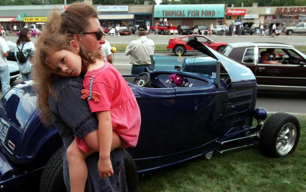 Description of . Joanne Saber of Lake Orion holds her granddaughter Ashley Saber,5,  as they look at classic cars along Woodward Ave. during the Fifth Annual Woodward Dream Cruise.