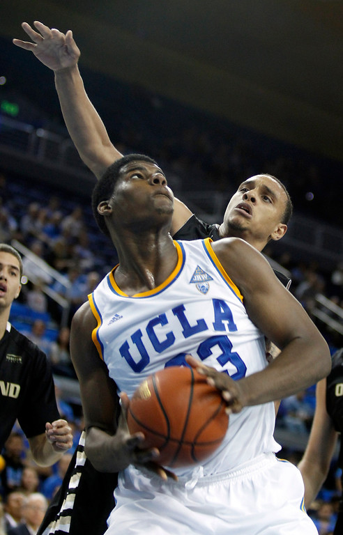 Description of . UCLA center Tony Parker, left, pulls up to take a shot with Oakland forward Tommie McCune, right, defending in the second half of an NCAA college basketball game Tuesday, Nov. 12, 2013, in Los Angeles. UCLA won 91-60.  (AP Photo/Alex Gallardo)