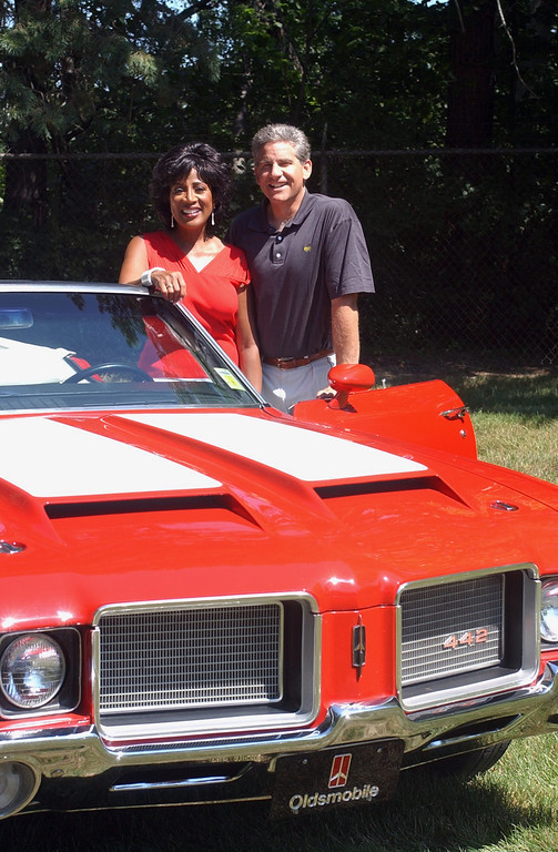 Description of . Diane Lewis and Guy Gordon from WXYZ-TV/channel 7 stand with a classic Oldsmobile for this year\'s  9th annual Woodward Dream Cruise.