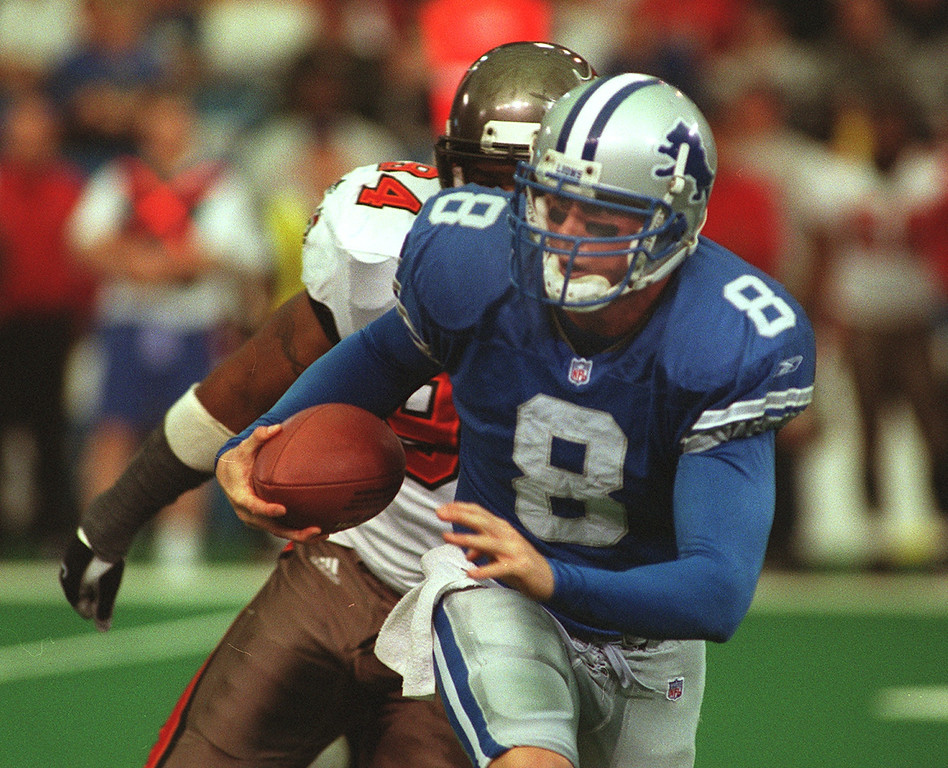 . Detroit Lions QB scrambles as Tampa Bay\'s DE Steve White closes in during Tampa\'s 20-17 victory over the Lioms at the Pontiac Silverdome Sunday.
