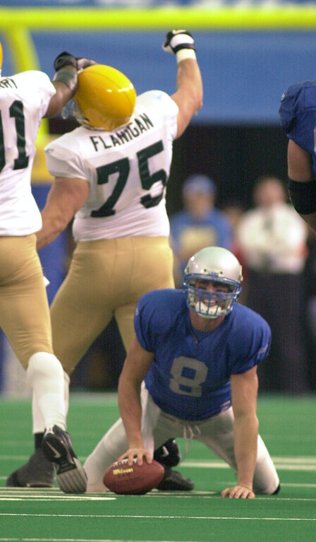. Detroit Lions quarterback Mike McMahon (bottom, #8) grimaces after being sacked as Green Bay Packers defensemen Jim Flanigan (middle, #75) celebrates with teammate John Thierry (#91)  , Thursday, November 22, 2001, in Pontiac, Mich.  The Lions lost to the Packers, 29-27.