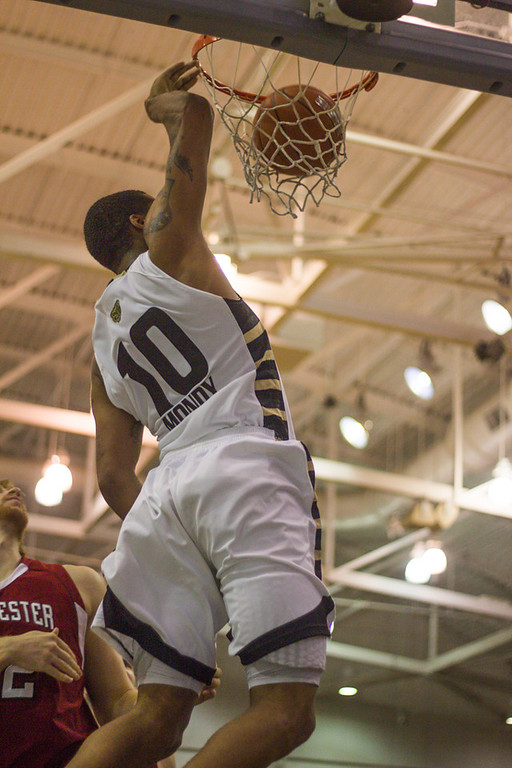 Description of . After a full-court breakaway, Mondy slam-dunks the ball during the second half. Photo by Dylan Dulberg