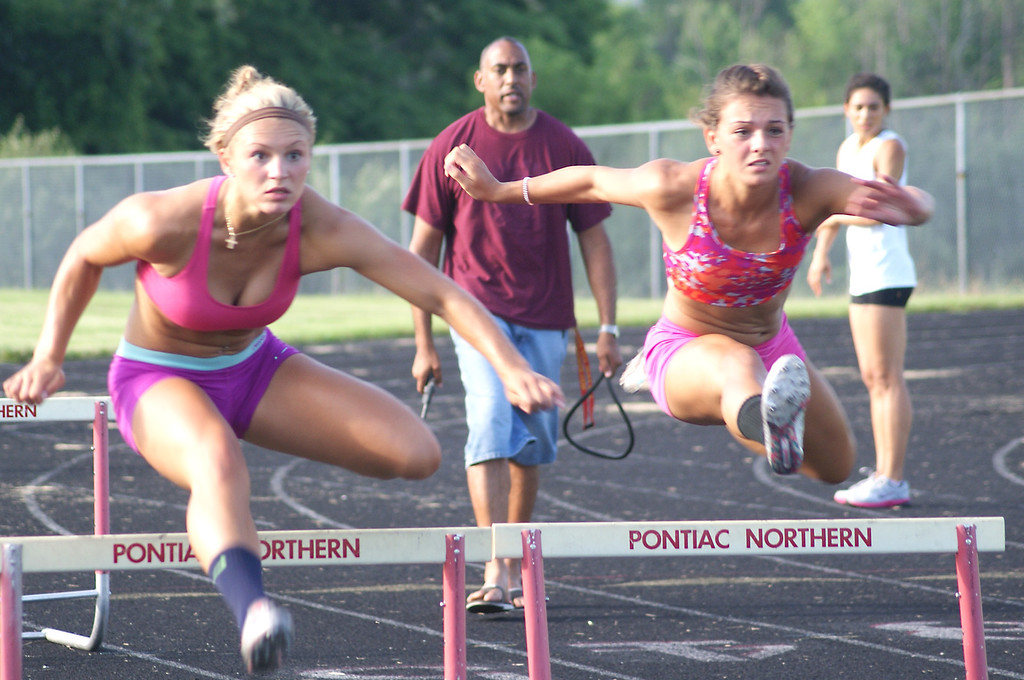 Description of . Allyson Goff (left) and Jessica Howell, members of the Elite Performance track and field club, clear the hurdles during a practice session Wednesday, July 17, 2013 at Pontiac High School. Both athletes qualified to compete at the USATF Junior Olympics, to be held July 22-28 on the campus of North Carolina A&T University in Greensboro, N.C.