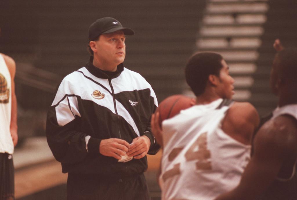 Description of . Oakland University men's basketball head coach Greg Kampe (left) watches his team run a play during practice, Thursday, November 12, 1998, at Oakland University.