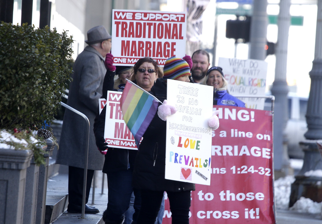 Description of . Supporters and protesters chant before closing arguments in the trial of two Detroit-area nurses, Jayne Rowse and April DeBoer, challenging Michigan's gay-marriage ban at the Theodore Levin Federal Court in Detroit Friday March 7, 2014. Michigan's ban on same-sex marriage was approved by voters in 2004.  Detroit federal Judge Bernard Friedman is not expected to make a decision Friday.  (AP Photo/Detroit Free Press, Mandi Wright)  DETROIT NEWS OUT;  NO SALES