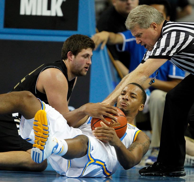 Description of . UCLA guard Norman Powell, center, pulls the ball away from Oakland center Corey Petros, left, in the second half of an NCAA college basketball game Tuesday, Nov. 12, 2013, in Los Angeles. UCLA won 91-60. (AP Photo/Alex Gallardo)