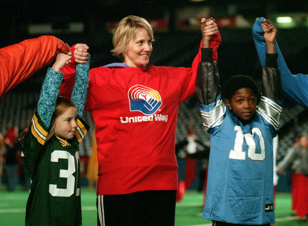 . While rehearsing their part in the United Way Halftime show at the Pontiac Silverdome Wednesday evening, Maggie Gallagher, 8 (left),  Debbie Hinkson, and Richerd Winton, 12 (right)), raise their hands in the air during the finale of Together We Stand.  Gallagher is wearing the jersey of Green Bay Packer Ahman Green , while Winton sports a Detroit Lions Charlie Batch shirt.  The two teams will meet Thanksgiving afternoon at the dome.