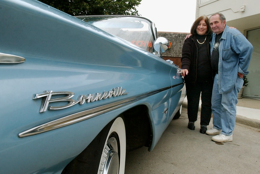 Description of . Betty, left, and Bob Kessel of Bloomfield Township, Mich., stand next to their 1960 Pontiac Bonneville.  Photo taken on Friday, August 13, 2004, in Birmingham, Mich.  They plan on parking their car along Woodward Avenue during the upcoming Dream Cruise.