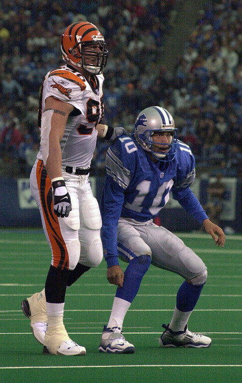 . Detroit Lions quarterback is helped off the turf by   Cincinnati Bengals player Justin Smith (90) during Sunday\'s game played at the Pontiac Silverdome. The Lions lost 31-27 to the Bengals.