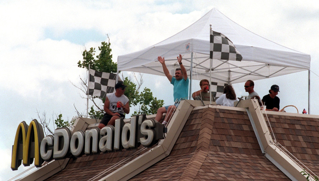 Description of . A group of people wave to passing cars from the Royal Oak McDonald's along Woodward Ave. during the Fifth Annual Woodward Dream Cruise.