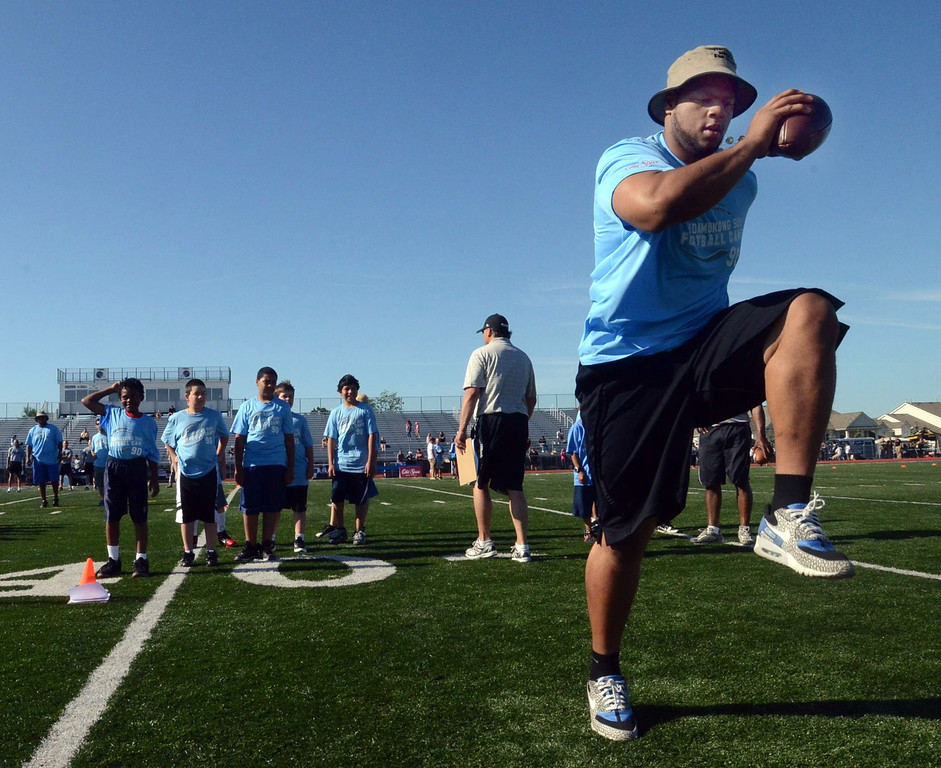 . Detroit Lions defensive tackle Ndamukong Suh demonstrates proper technique during stretching exercises at his football camp for kids at Walled Lake Western High School, Wednesday June 29, 2011. (Oakland Press Photo: Vaughn Gurganian)