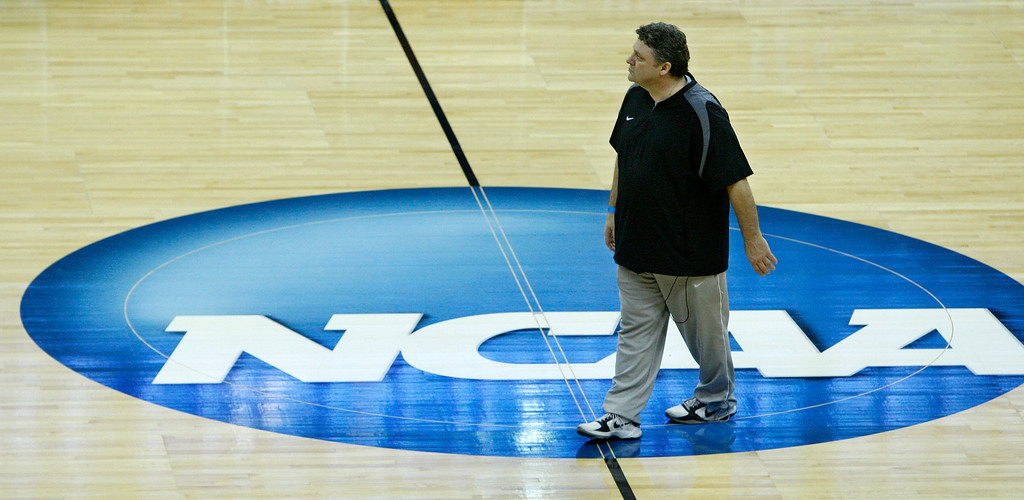 Description of . Oakland head coach Greg Kampe walks across the NCAA logo during a practice for the West regional second round NCAA college basketball tournament in Tulsa, Okla., Thursday, March 17, 2011. (AP Photo)