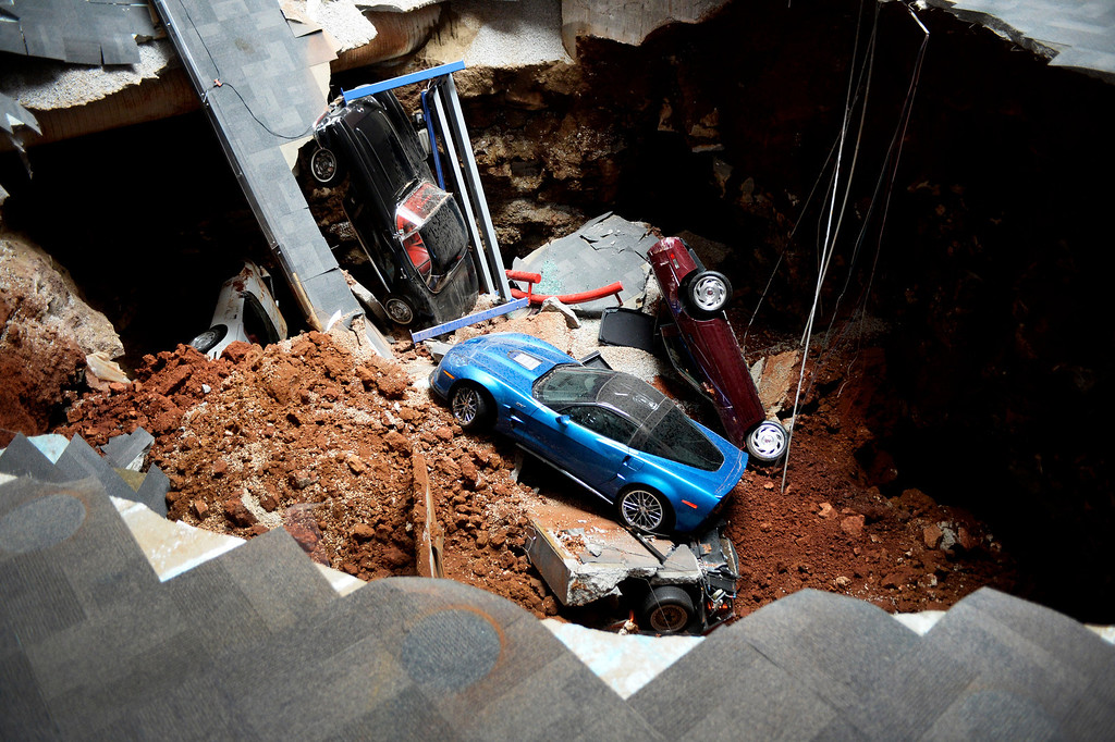 Description of . A view of a sinkhole that opened up in the Skydome showroom, Wednesday, Feb. 12, 2014, at the National Corvette Museum in Bowling Green, Ky. Eight display cars were swallowed by the hole. (AP Photo/Michael Noble Jr)
