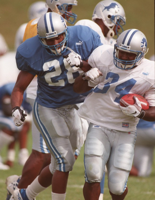 . Detroit Lions safety Ron Rice (left, #28) gives a friendly shove to teammate Ron Rivers (#34) during practice, Monday, August 9, 1999.
