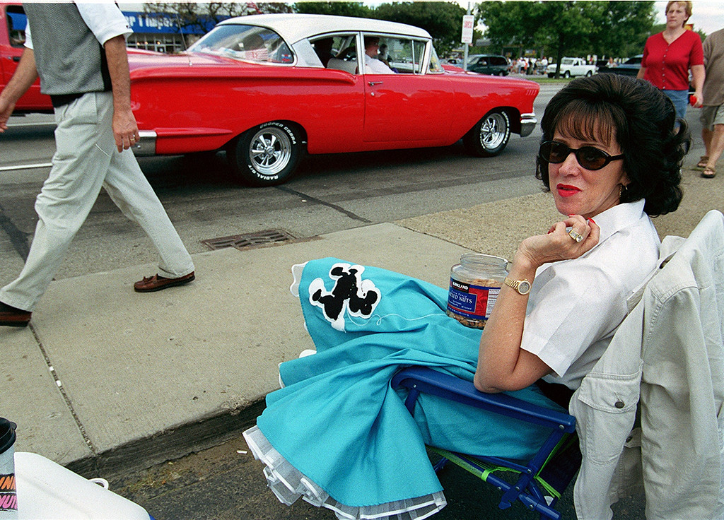 Description of . Dressed in a poodle skirt, classic car owner Jackie Van Cura snacks on nuts as she watches the vintage cars parade down Woodward during the annual Dream Cruise.