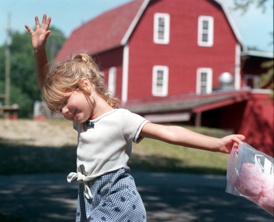 Description of . In between mouthfuls of cotton candy, Amanda Mertz, 4,  plays outside the Yates Cider Mill yesterday afternoon.