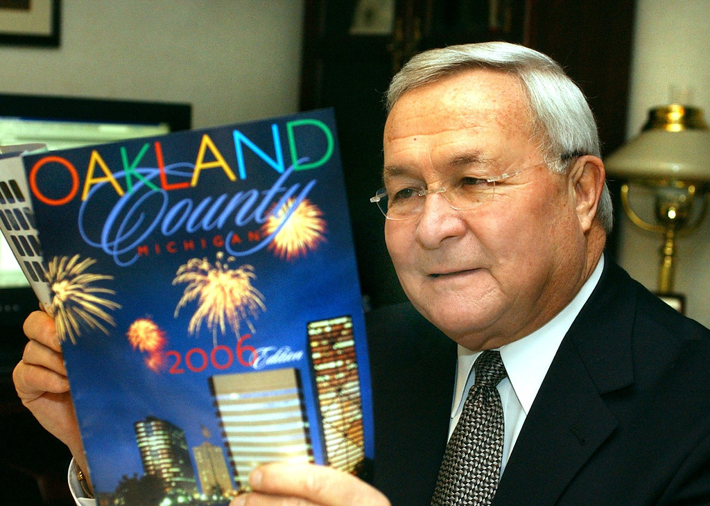 Description of . Oakland County Executive L. Brooks Patterson looking over a guide to Oakland County.