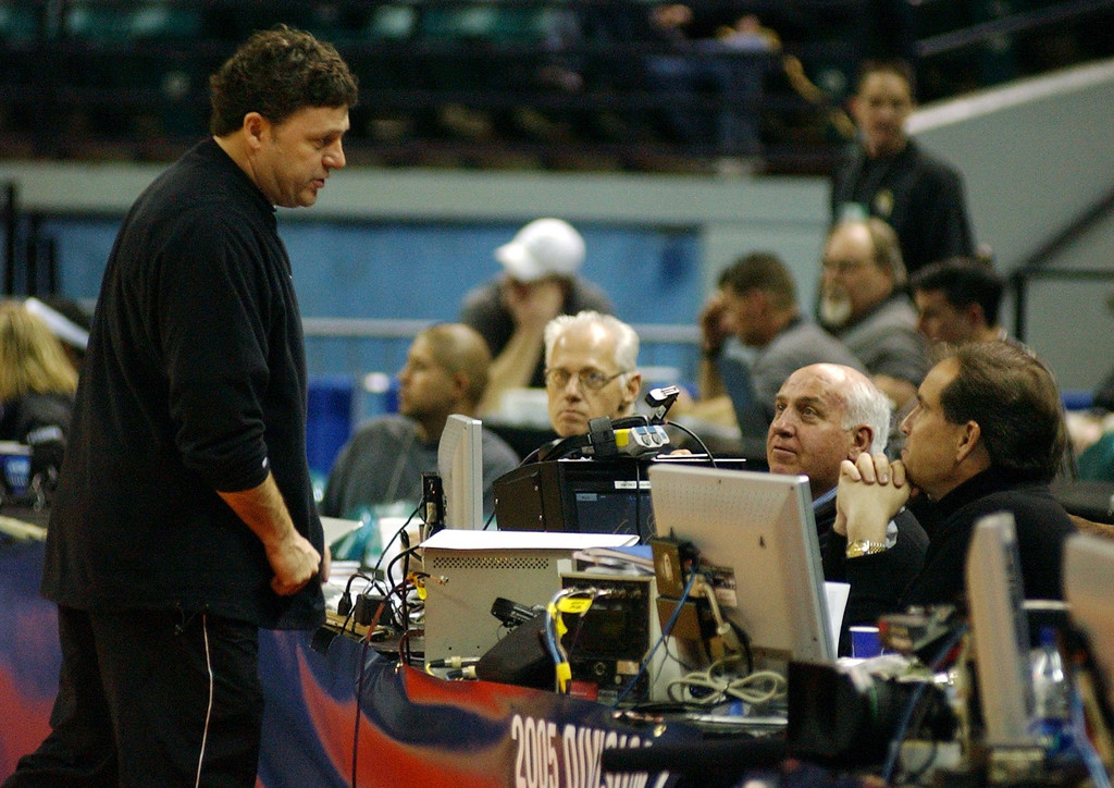 Description of . Oakland University men's basketball head coach Greg Kampe, left, chats with CBS sports commentators Billy Packer, right, and Jim Nantz, far right, at the end of his team's practice, Thursday, March 17, 2005, at the Charlotte Coliseum in Charlotte, NC.