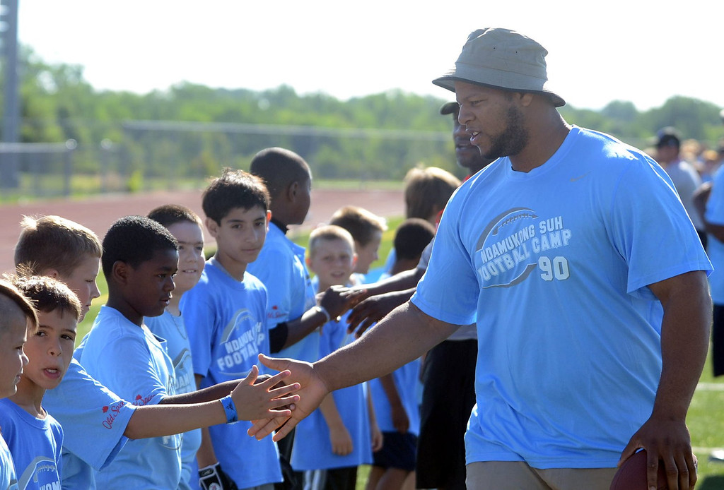 . Detroit Lions defensive tackle Ndamukong Suh greets kids during his football camp for kids at Walled Lake Western High School Tuesday June 28, 2011. (Oakland Press Photo: Vaughn Gurganian)