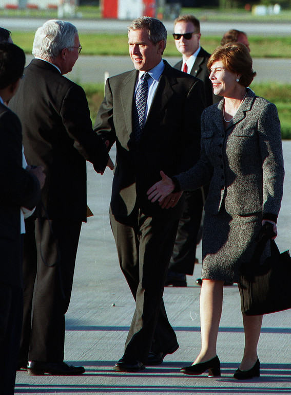 Description of . Republican Presidential candidate Gov. George W. Bush, center, and his wife Laura greet Oakland County Executive L. Brooks Patterson during Bush's stop over at the Oakland County International Airport in Waterford.