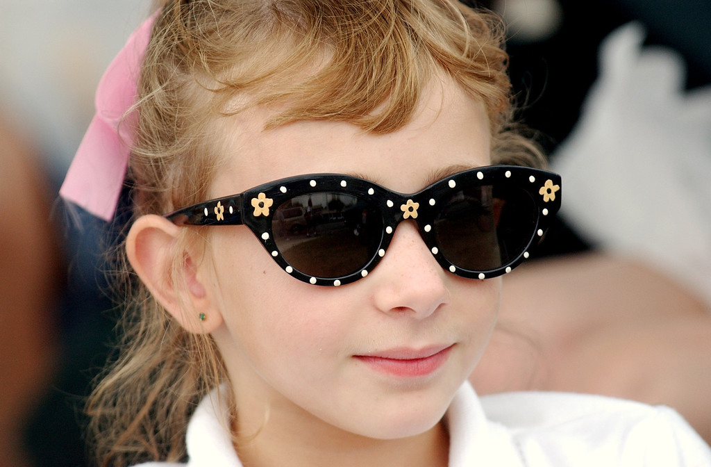 Description of . Emma West, age 9, of Romeo, Mich., watches cars as she is dressed wearing a 1950\'s style of clothing during the Dream Cruise.  Photo taken on Saturay, August 20, 2005, in Royal Oak, Mich.