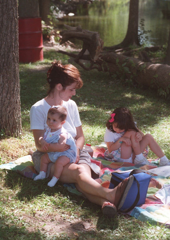 Description of . Kristin Roodbeen picnics with her daughters Jillian ,5 months, and Natalie,4, near the water at Yates Cider Mill in Rochester Hills.