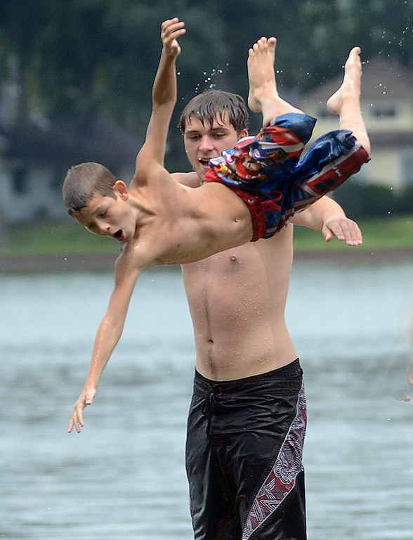 Description of . Anthony Caizza, 10, goes flying into the air after being playfully thrown in by Jeremy Haynor, both of Commerce Township, while spending the afternoon cooling off in Long Lake in Commerce Township, Monday July 22,2013. (Oakland Press Photo:Vaughn Gurganian)