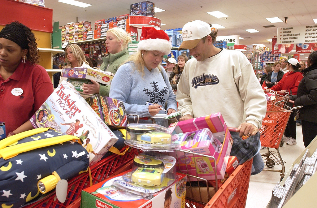 Description of . Shoppers at the Target store behind Summit Place Mall were packing the isles early this morning when it opened it's doors at 6:00am. This is Lynn and Jim Ostrowski of Waterford checking their Christmas list with two carts full of toys as other shoppers whiz around them looking for the bargins.
