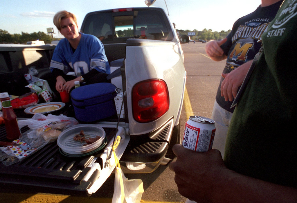 Description of . A unidentified man holds a beer as Cindy Neal of Clinton Twp. tailgates before the start of the Detroit Lions Monday nights game against the Tampa Buccaneers at the Pontiac Silverdome.