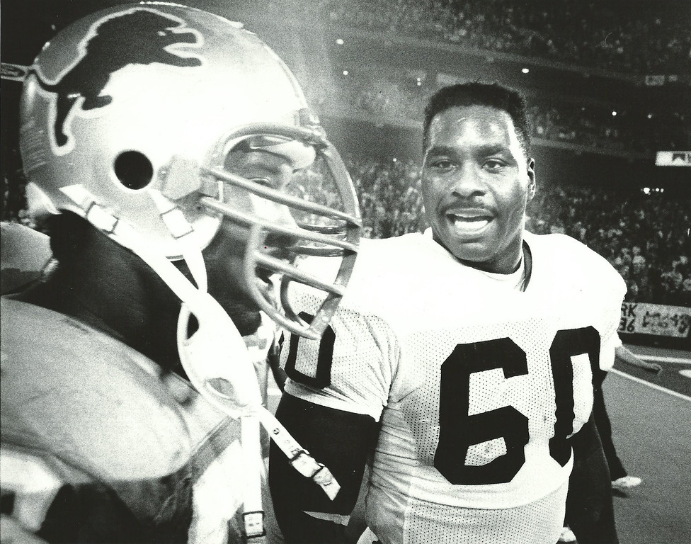 Description of . Former Detroit Lions player Reggie Rogers (right) talks to a teammate in Nov. 1989. Oakland Press file photo