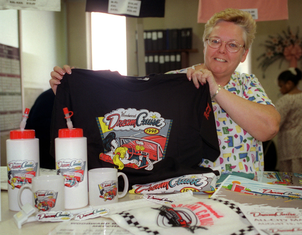 Description of . Marsha Mellert, Recreation supervisor at Ferndale City Hall, shows off some of the Dream Cruise merchandise (T-shirts, mugs, keychains, car flags, etc) for sale at the city's Dept of Public Services and Recreation.