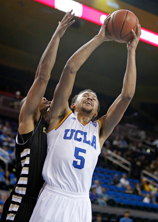 Description of . UCLA guard Kyle Anderson (5) shoots as Oakland forward Ralph Hill defends during the second half of an NCAA college basketball game Tuesday, Nov. 12, 2013, in Los Angeles. UCLA won 91-60.  (AP Photo/Alex Gallardo)