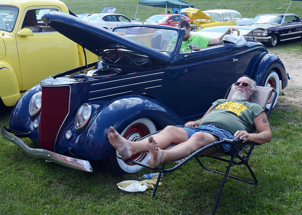 Description of . Jim Simmons, of Davisburg, catches a little nap next to his 1936 Ford Roadster along  Woodward Avenue in Pontiac during the 2013 Woodward Dream Cruise, Saturday August 17, 2013. (Oakland Press Photo:Vaughn Gurganian)