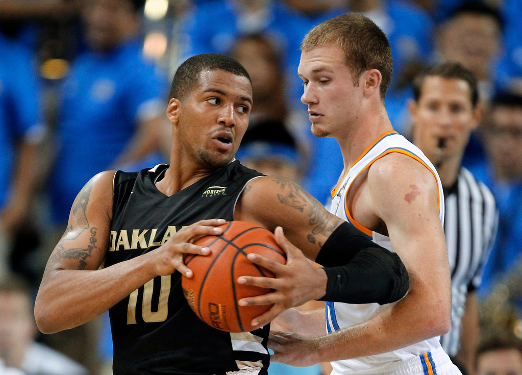 Description of . Oakland guard Duke Mondy, left, takes the ball around UCLA guard Bryce Alford during the second half of an NCAA college basketball game Tuesday, Nov. 12, 2013, in Los Angeles. UCLA won 91-60. (AP Photo/Alex Gallardo)
