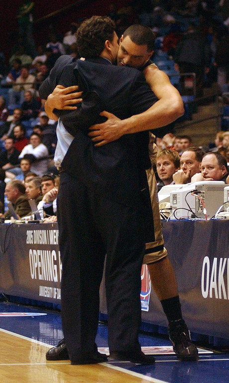 Description of . Oakland University men's basketball head coach Greg Kampe, left, hugs Cortney Scott near the end of their game against Alabama A&M during second half action of an opening round game, Tuesday, March 15, 2005, at the University of Dayton Arena in Dayton, Ohio.  Oakland beat Alabama A&M, 79-69, and will now play North Carolina on Friday, March 18.