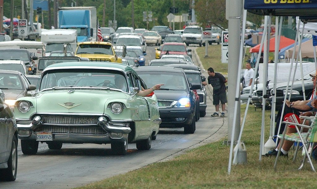 Description of . Motorists drive through the rain after making the loop onto southbound Woodward, during the Dream Cruise.  Photo taken on Saturday, August 21, 2010, in Pontiac, Mich.  (The Oakland Press/Jose Juarez)