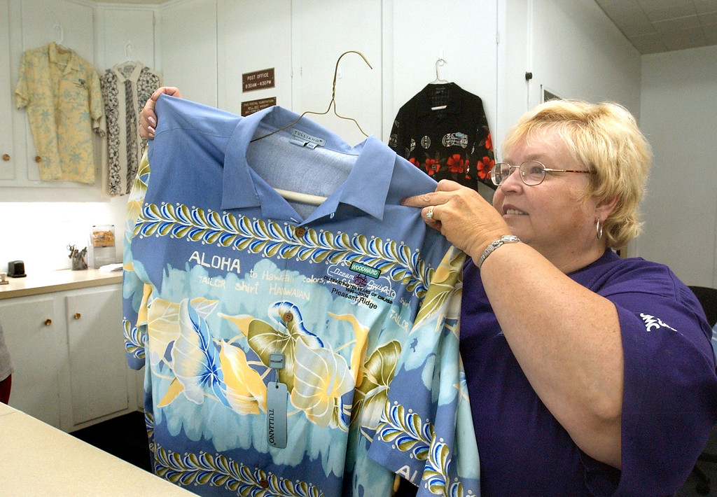 Description of . Shirley Reese, Woodward Dream Cruise Coordinator for Pleasant RIdge, shows of a Hawiian shirts that are for sale at City Hall.  The shirts are $60.00 with XXL $65.00.
