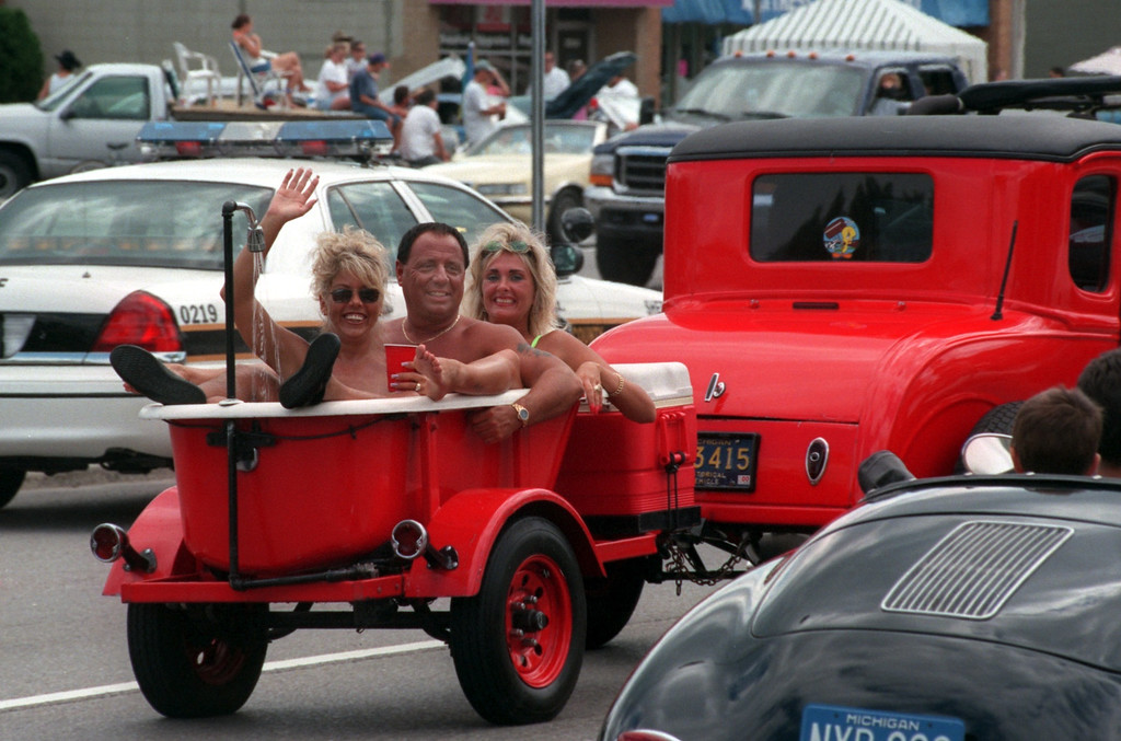 Description of . A threesome in a tub make their way down Woodward Ave. during the Fifth Annual Woodward Dream Cruise.