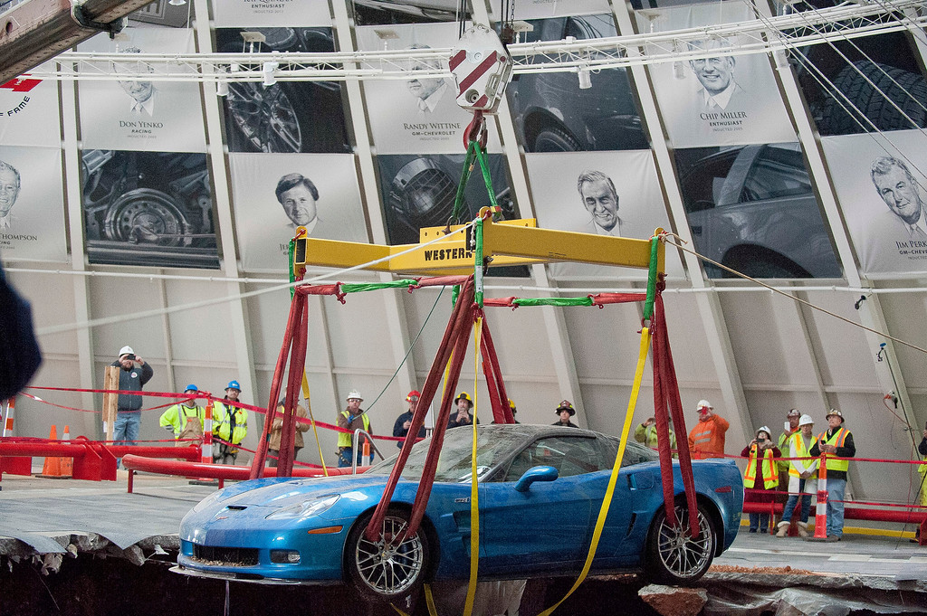 Description of . One of eight Chevrolet Corvettes is removed from a sinkhole in the Skydome at the National Corvette Museum, Monday, March. 3, 2014, in Bowling Green, Ky.  On Feb. 12, a large sinkhole swallowed eight prized cars like they were toys, piling them in a heap amid loose dirt and concrete fragments. (AP Photo/Daily News, Alex Slitz)