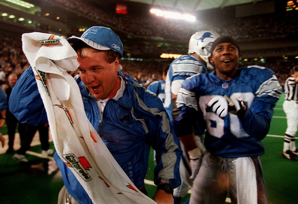 . Drenched with ice water by his players, Detroit Lions Head Coach Marty Mornhinweg (left) towels off as he celebrates with Desmond Howard (right) the team\'s first win of the season after a 27-24 defeat of the Minnesota Vikings at the Silverdome Sunday.