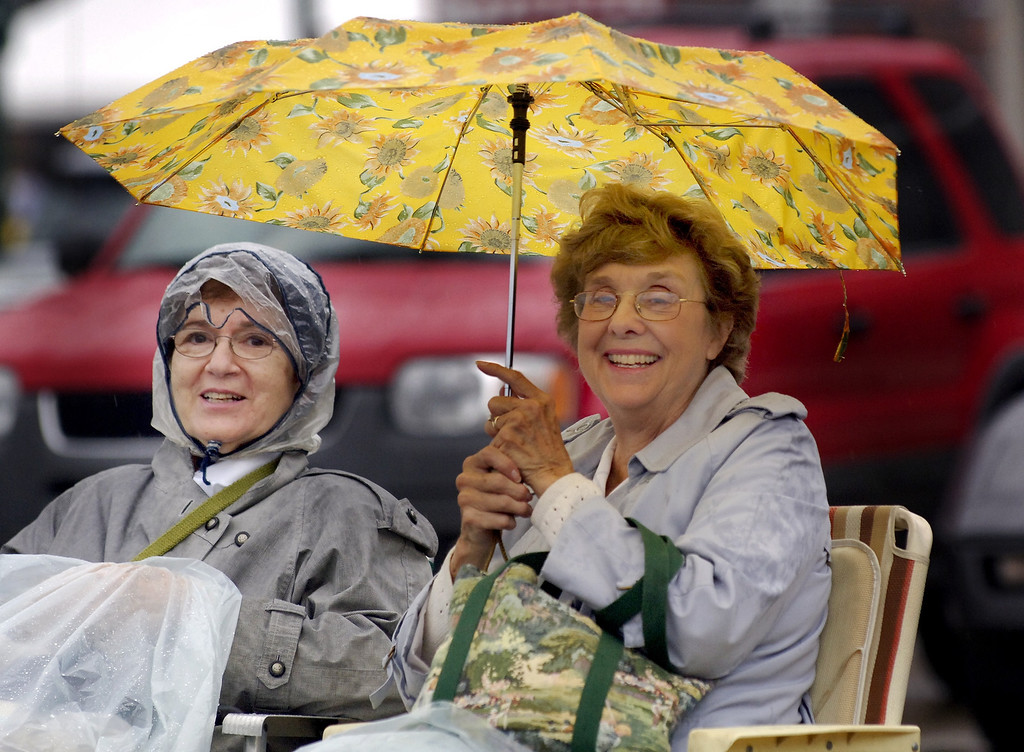 Description of . Katherine Gribbs (left) of Northville and friend Janet Dulmage of Orchard Lake sit in the rain Saturday morning onlong Woodward near 15 Mile Rd. waiting for cruisers to start passing by.