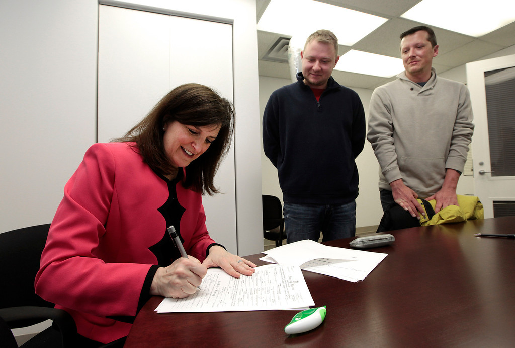 Description of . Oakland County Clerk Lisa Brown signs a marriage license for Justin Flowers, middle, and Josh Redder after performing their wedding ceremony at the Oakland County Clerks office in Pontiac, Mich., Saturday, March 22, 2014. A federal judge has struck down Michigan's ban on gay marriage Friday the latest in a series of decisions overturning similar laws across the U.S. Some counties plan to issue marriage licenses to same-sex couples Saturday, less than 24 hours after a judge overturned Michigan's ban on gay marriage. (AP Photo/Paul Sancya)